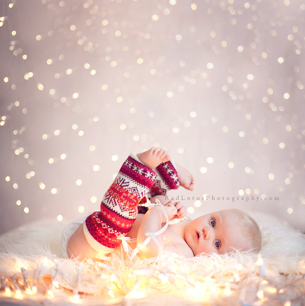 baby in front of a twinkle light backdrop