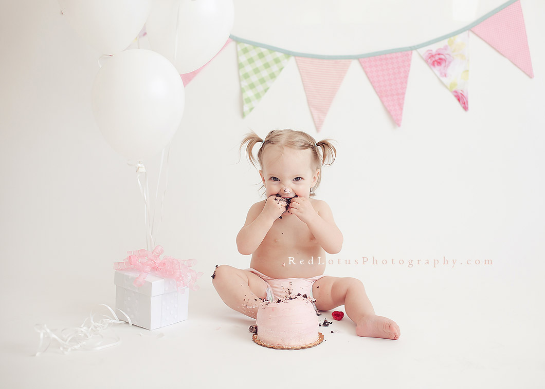 One year old toddler girl with smash cake