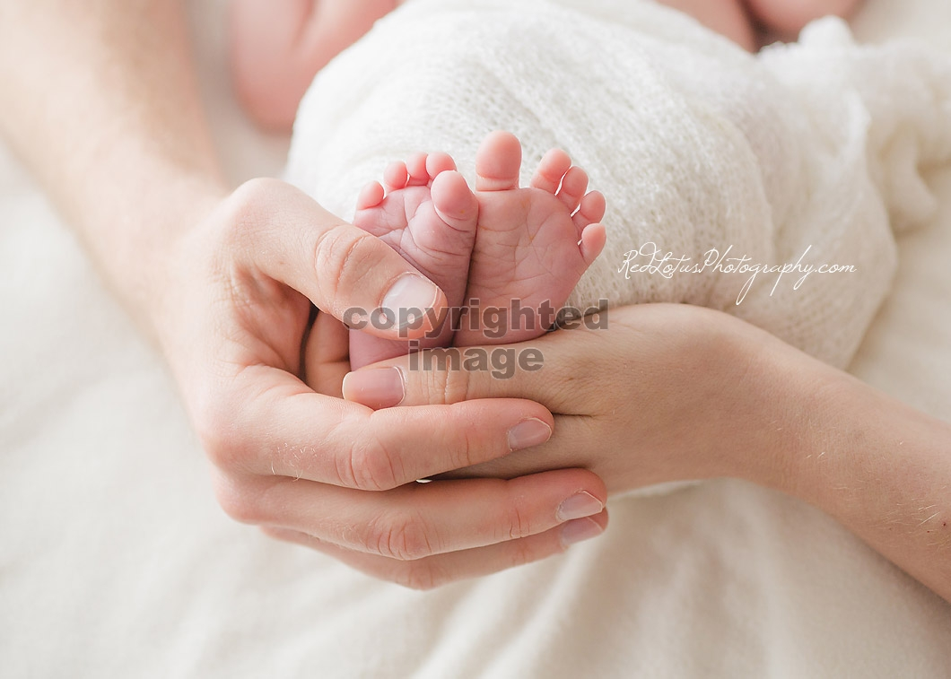 baby feet held by hands